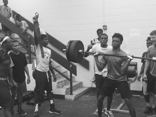 "Lincoln Trojans football players cheer each other on in a power cleans battle during summer workouts last week, on a day dubbed ""Competition Thursday."""