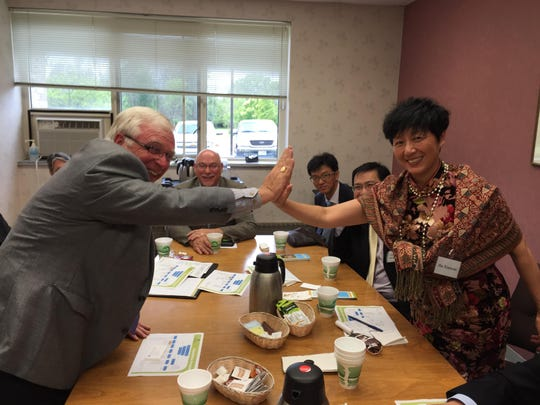Ministry Door County Medical Center CEO and President Gerry Worrick high-fives Jingdezhen No. 1 People's Hospital Director Hu Xiaoyan during a meeting at the hospital on Tuesday.