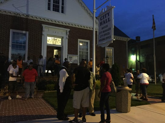 People stand outside Pocomoke City Hall on Monday night after a meeting during which residents spoke to the mayor and city council about fired Police Chief Kelvin Sewell.