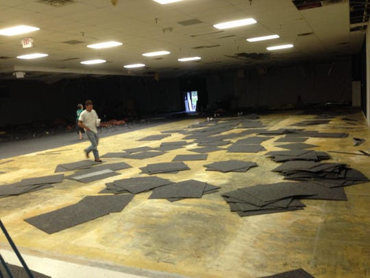 Workers dismantle the ceiling of a former indoor tennis