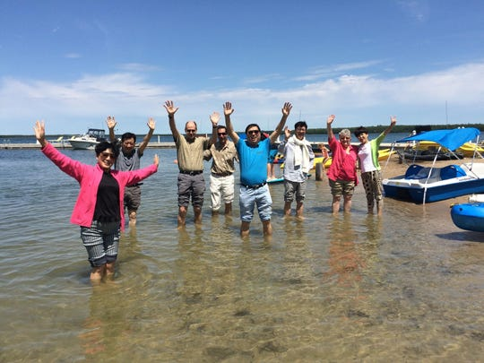 Chinese delegates step into the waters of Lake Michigan for the first time from North Bay with Door County natives at Gordon Lodge.