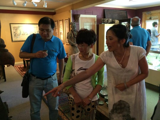 Jeanee Linden, right, talks about pieces in the Linden Gallery with Parker, left, and Fang Ping.