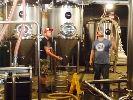 An employee and head brewer Randy Mills, right, check out the mash tun.