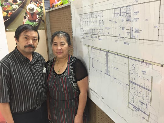 Chungsou Her and Mai Her stand next to plans of the Wausau World Market at Phou Bia Oriental Market.