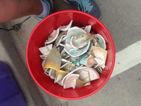 A 5-gallon bucket full of ceramic shards are all that remain of much of Mary Merrill's pottery after strong gusts of wind damaged her booth at the Midsummer Arts Festival.