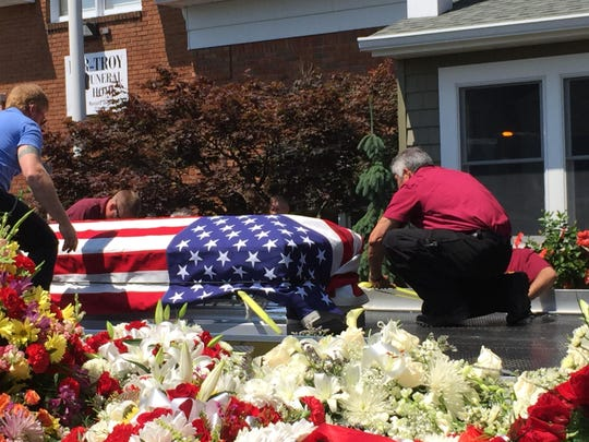 "The casket of Robert Paul ""Butch"" Hubert is loaded onto a tow truck Monday July 20 at Par-Troy Funeral Home in Parsippany. About 40 tow trucks joined the procession to the cemetary."