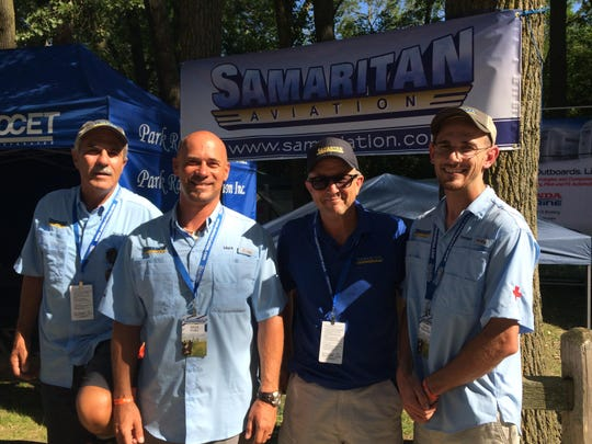 FROM LEFT: Bruce Johnson, Mark Palm, Bryan Yeager and Forrest Williamson all of Samaritan Aviation, which provides medical care via seaplane Papua New Guinea, set up a booth to seek funding at EAA AirVenture.