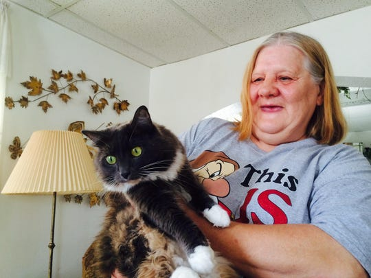 Gloria Johnson holds her cat Sad Eyes in her Fulton Street home on July 22, 2015. Johnson adopted the cat from a stray she calls Vagabond who's had many litters in recent years.
