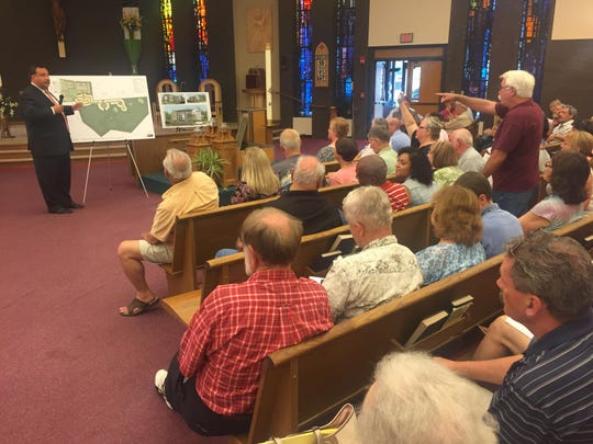 Developer attorney Larry Tarabicos explains the layout of the Our Lady of Grace housing development, off Chestnut Hill Road, near Newark, as residents look on at a public meeting Thursday at Holy Family Church near Newark.