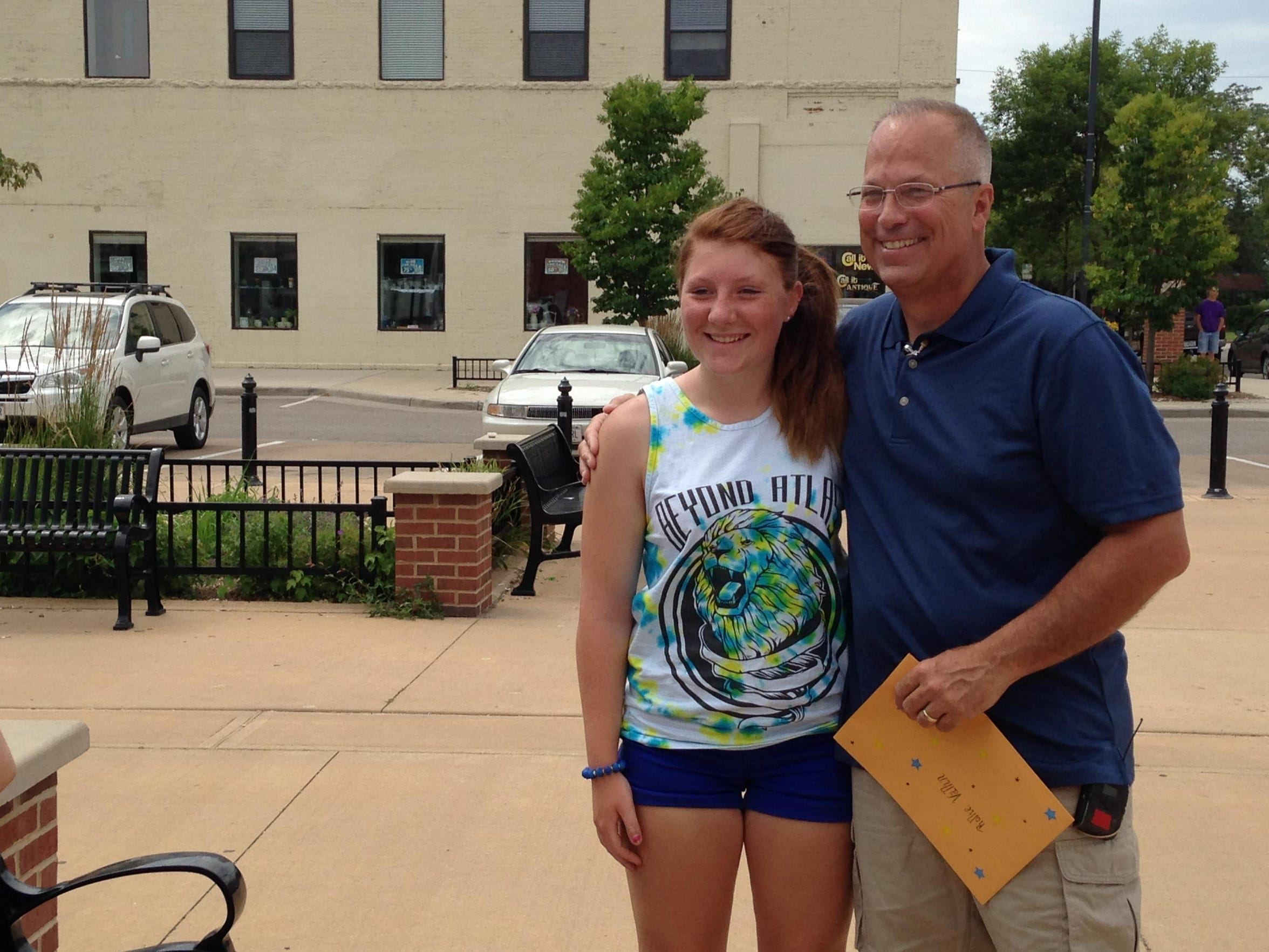 Jordin Rasmussen, left, and Rollie Vallin reunited on the Mathias Mitchell Public Square July 26. Vallin holds an envelope that contains information on the star the Rasmussen family named after him.