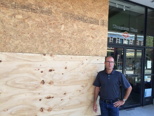Woolworth Walk owner Scott Sirkin stands beside a board-up window, which was broken by a street dancer Sunday. Aug. 3, 2015