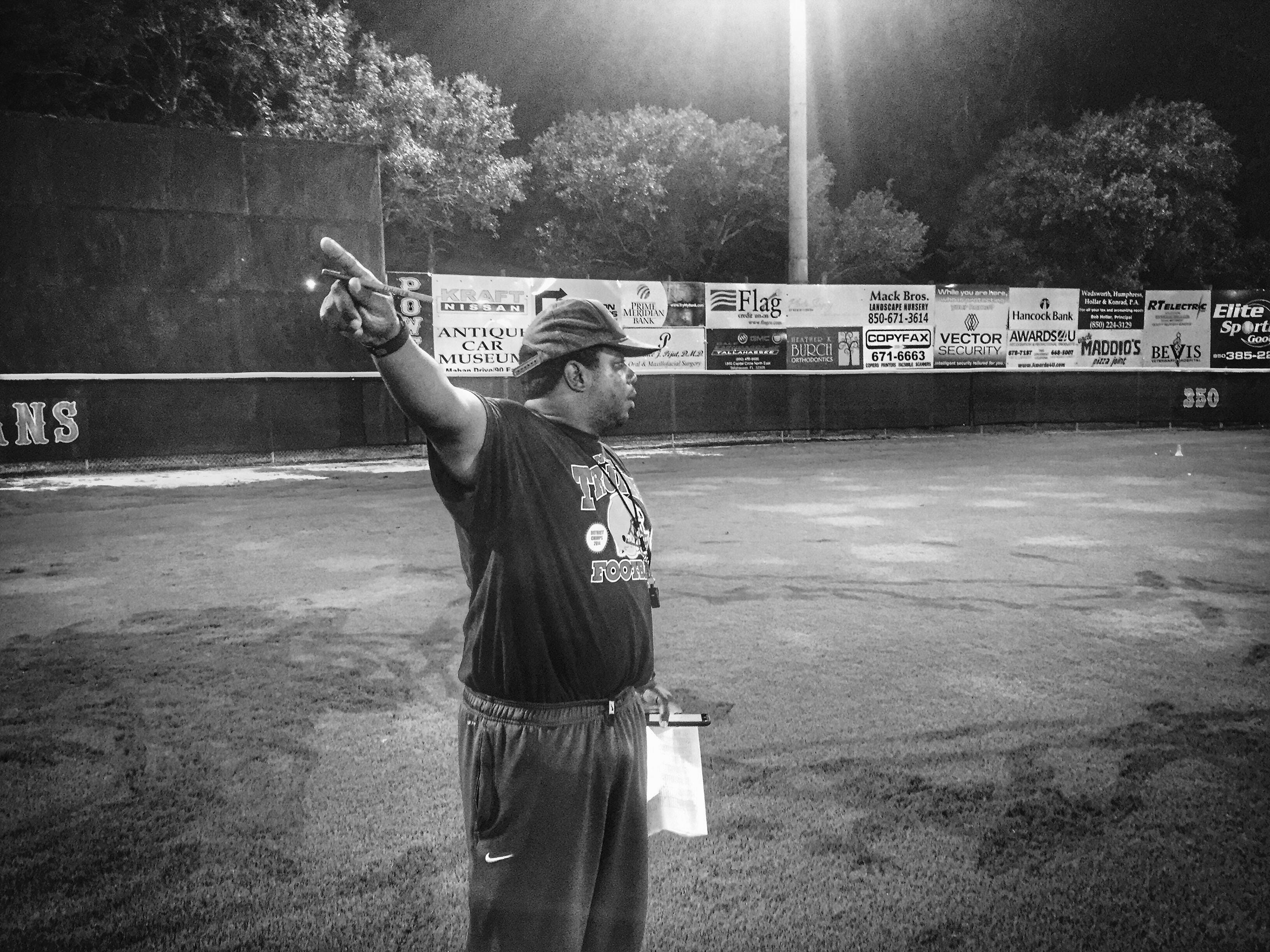 Lincoln head coach Yusuf Shakir directs players where to go during Midnight Madness drills for the start of the fall football season.