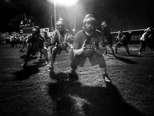 Lincoln offensive lineman Casey Warming works in unison with the rest of his o-line during Midnight Madness drills to mark the start of the fall football season.