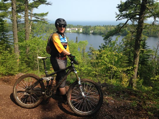 Lori Hauswirth, executive director of the Copper Harbor Trails Club, poses with her bike in front of Lake Fanny Hooe and Fort Wilkins.