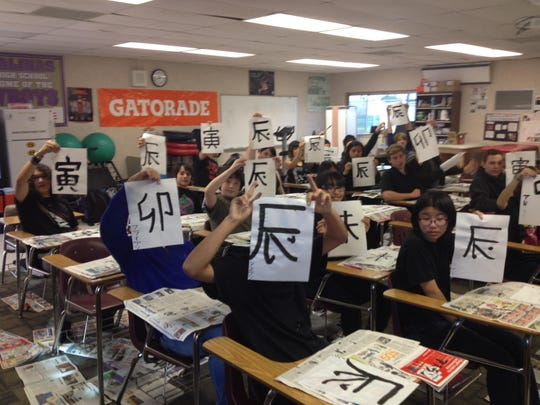Students in a first-level Japanese class at Salinas High School display their calligraphy as they learn about Japanese New Year activities in January.