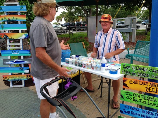 """JR Norman paints small, personalized """"beach bum"""" paintings at Times Square in Fort Myers Beach."""