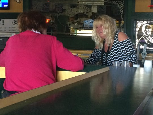 Marjean Gable, who has tended bar at Packers Pub for 12 years, takes a drink order. Packers Pub will close Aug. 15 after 38 years in business.