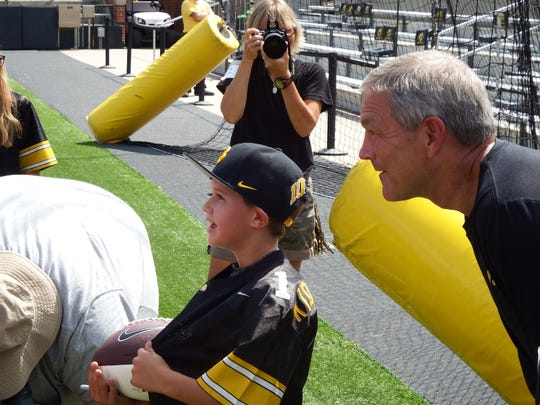 UI Hawkeye head coach Kirk Ferentz poses with Kid Captain Colton Barker, 8, of Sioux City as Nola Riley of UIHC takes a photo at Kinnick Stadium on Aug. 15.