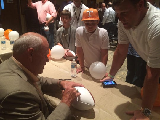 Former Tennessee coach Phillip Fulmer signs a football