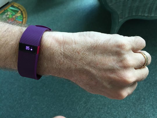 A diabetes patient wears a wrist monitor at home, which displays his heart rate.
