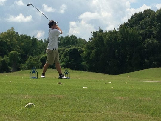 A golfer from Trenton Peabody follows through on his