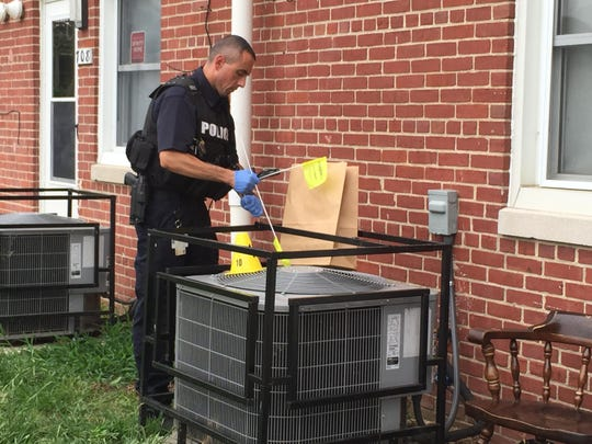 Master Sgt. Adam Ringle, in charge of the investigation in the 700 block of Townsend Place, bags a piece of evidence, believed to be a T-shirt, from behind an air-conditioner of another home on the block.