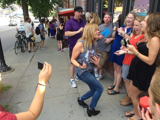 "Grace Potter hands out Swedish fish to fans waiting Thursday outside Pure Pop Records in Burlington, where she signed copies of her new album, ""Midnight."""