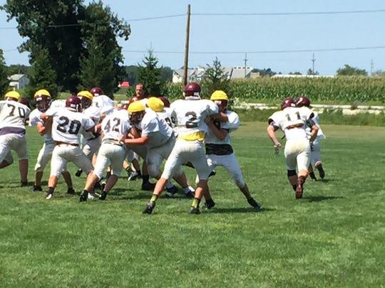 Genoa's Michael Roberts, right, rushes the quarterback during a preseason practice.