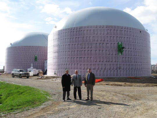 Tom Sonnleiter, UWO vice chancellor for administrative services; Art Rathjen, president of UWO Foundation; and Jim Ostrom, one of the Milk Source partners, pose in front of the two methane biodigesters, each capable of holding a million gallons.