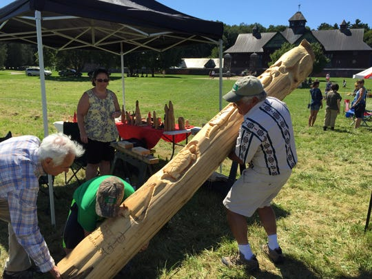 Richard Menard of Highgate raises a completed totem pole that he carved on the grounds of Shelburne Farms during the Wabanaki Confederacy conference on Saturday.