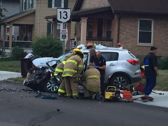 Emergency personnel extricate the female driver of a Kia Sportage involved in a head-on crash.