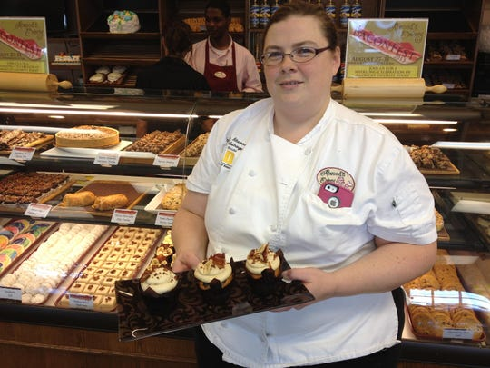Jennifer Atwood displays a tray of Elvis Cupcakes and Beer'n Bacon Cupcakes during the first year of BaconFest at Atwood's Bakery.