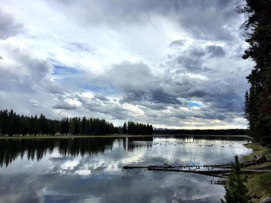 Storm clouds reflect in the Yellowstone River in Yellowstone National Park.