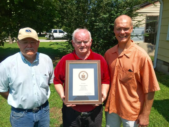 William Brantley, center, receives an award recognizing his 10 years of volunteer service with the National Weather Service from Zwemer Ingram, left, data acquisition program manager, and Jim Belles, chief meteorologist in charge with the weather service in Memphis.