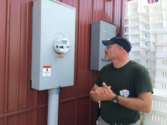 Layton's Chance owner and winemaker William Layton checks the readout on the vineyard's new solar energy monitor. Layton says the panels will generate enough power to fulfill about 70 percent of the winery's energy needs.