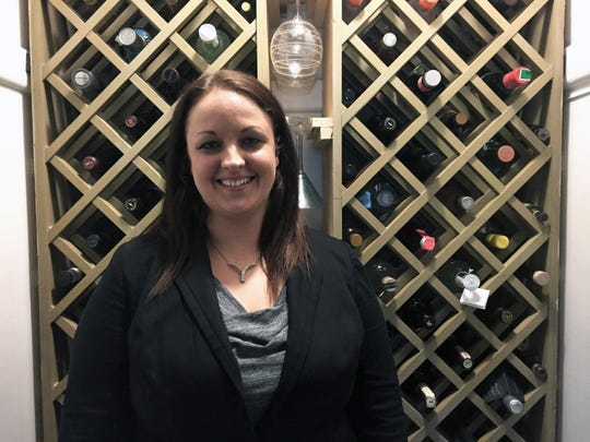 Jessica Taylor stands in front of built-in storage for liquor in her home closet.
