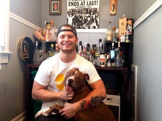 Ryan Puckett, bartender at Libertine, shows off his home bar with his dog Django.