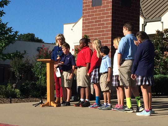Music teacher Elizabeth Atkins leads students in telling the history of the national anthem at the University School of Jackson Monday.
