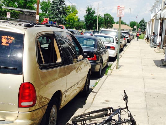 A tan minivan on the south side of the 800 block of Wallace Street was damaged by gunfire, which shattered a window, on Sunday afternoon. Police seized the 10-speed bicycle seen near the ban as evidence.