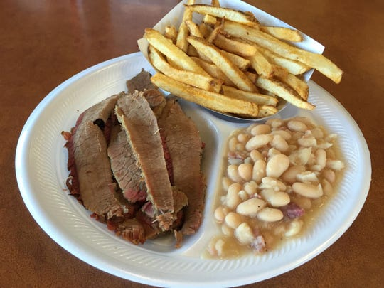 Beef brisket served with white beans and fresh-cut potato fries.
