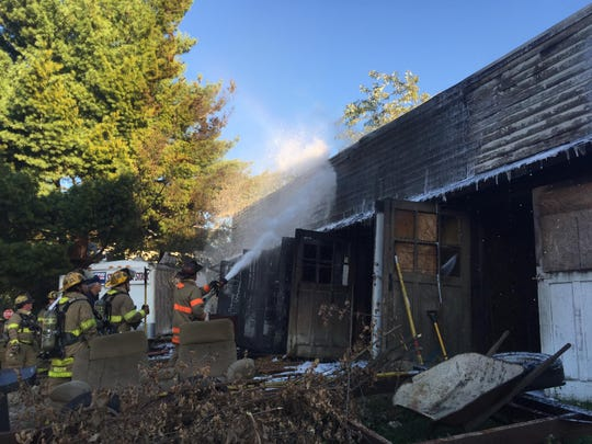 Firefighters spray down hot spots after a Monday afternoon fire destroyed a garage at 490 S. Main St.