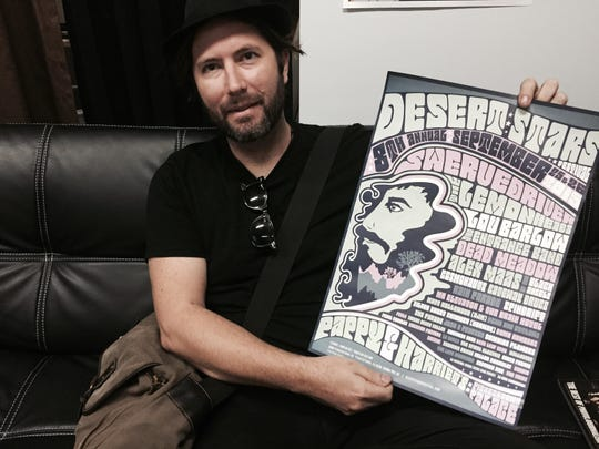 Tommy Dietrick, promoter of the Desert Stars Festival, shows off a poster for a past festival during a visit to The Desert Sun office.