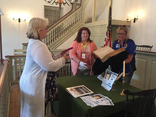 """Cindy Snyder, center, who supervises the New Castle Courthouse Museum, helps Diva Darlings team members Pati Wright, right, and Carrie DeLeon get their photographic proof of having been the first """"Fireball Run"""" team to find George Read's law book, one of three historic points of interest they searched for Sunday."""