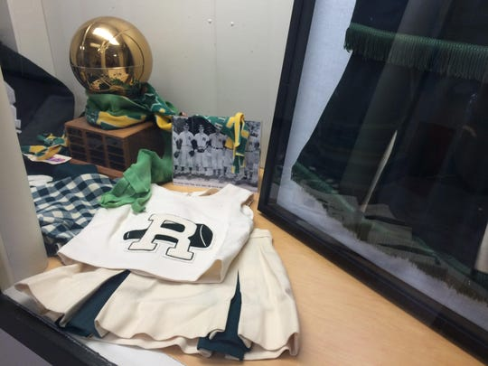 A cheerleading uniform and photos from Rice Memorial High School's past are on display in new trophy cases. The new cases are part of a $12 million renovation at the Burlington school.