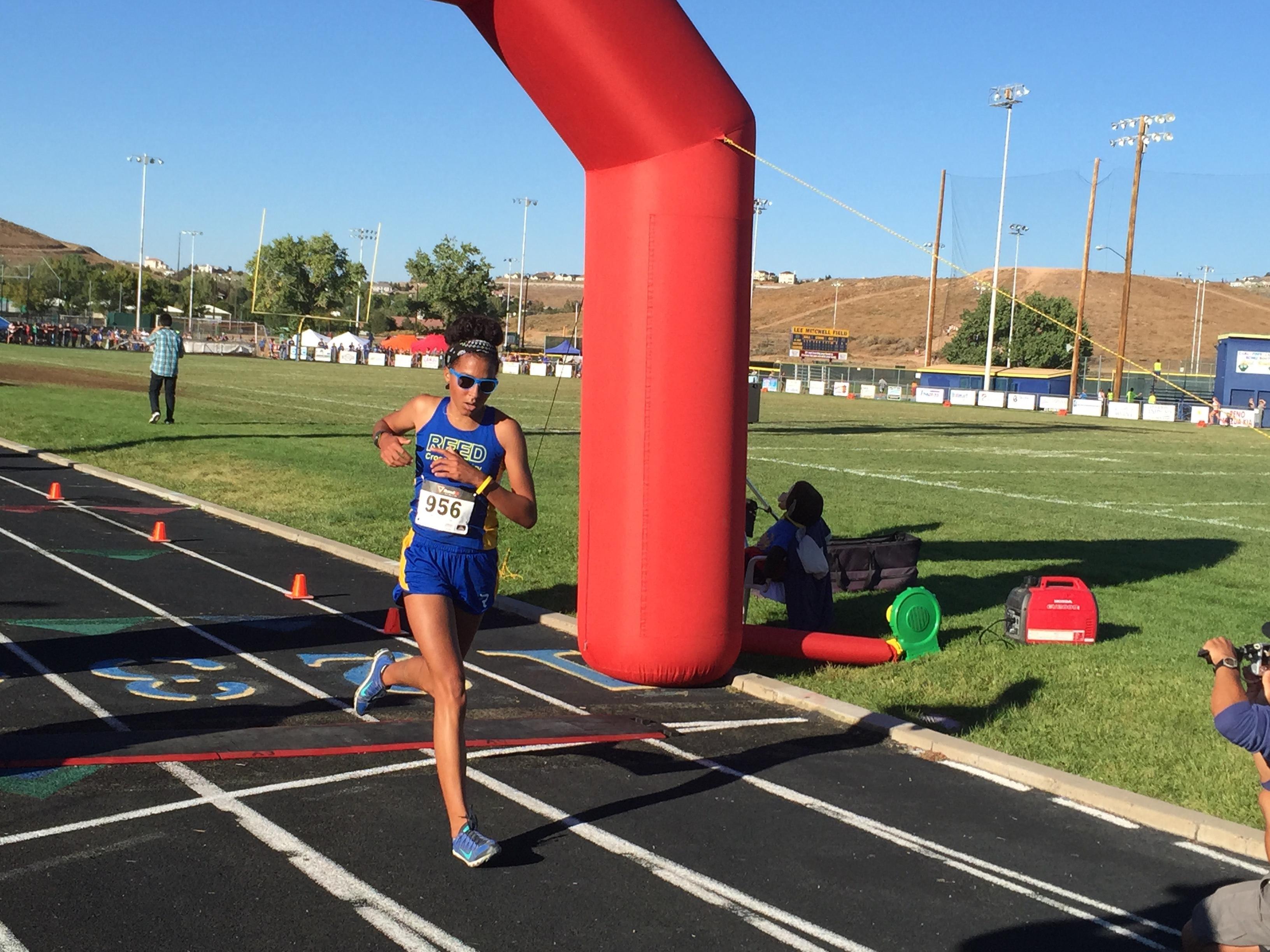 Reed junior Samanatha King-Shaw crosses the finish line Friday at Reed
