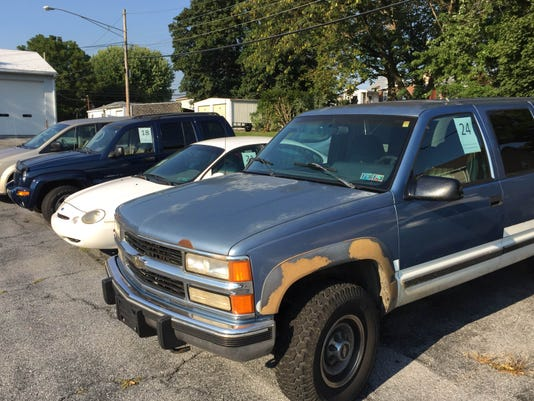 Older model vehicles owned by the county are parked in a lot on Oak Street in Lebanon. They are numbered for sale at auction.
