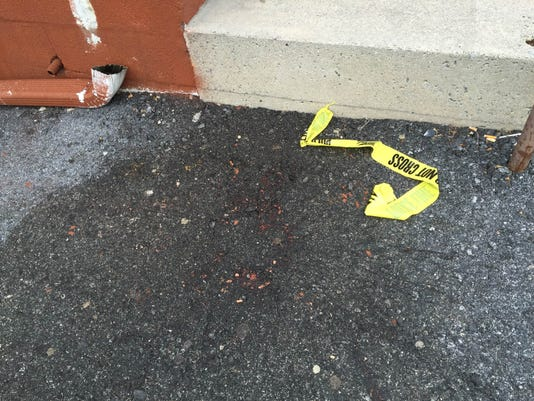 A scrap of police tape lies on the pavement in the parking lot at Vinny's Goodtimes bar at N. Seventh and Reinhoehl streets where police say a man was shot and killed early Saturday morning.