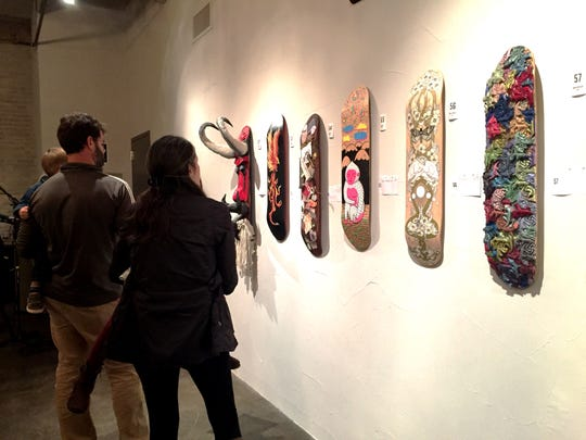 Guests at The Parliament's third annual Decked Out fundraiser look at hand-painted, collaged and manipulated skate decks on display at The Bond in York on Oct. 17, 2015. More than 130 skate decks from six Central Pa. art galleries were auctioned off.