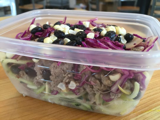 The BFF bowl, here packaged to go, layers ground turkey, red cabbage, zucchini noodles, black beans, corn, avocado and brown rice.