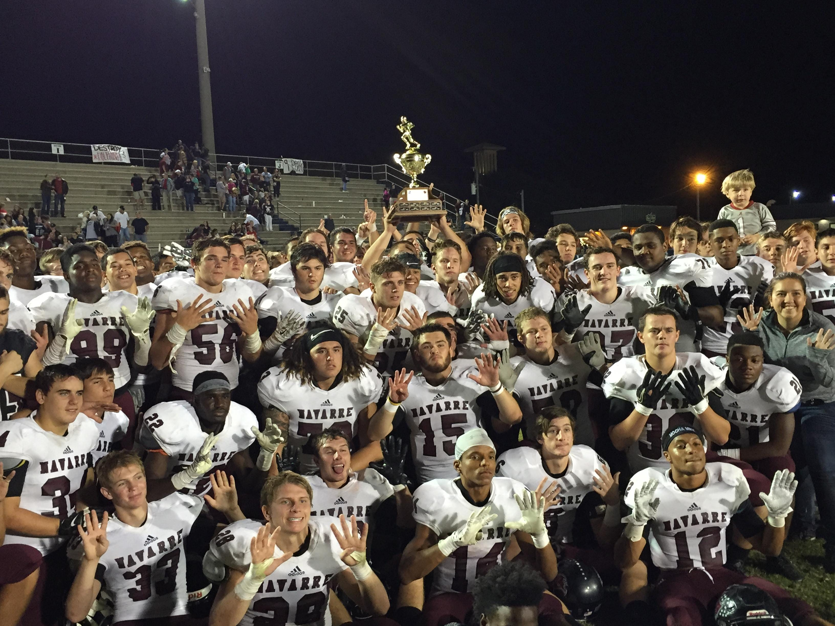 Navarre Raiders players hold up nine fingers and the Beach Ball Trophy to signify the nine-game win streak they currently hold over Gulf Breeze after Friday's 47-7 rout.